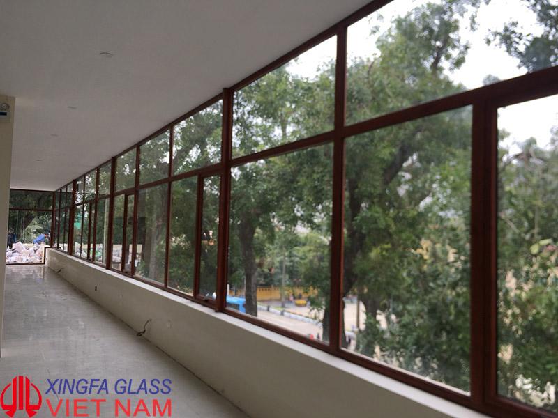 Vách kính cố định kết hợp cửa sổ mở hất nhôm Xingfa màu vân gỗ